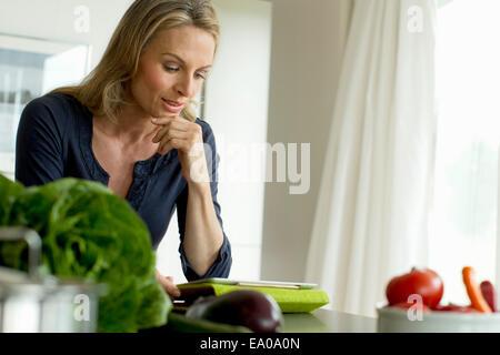 Mature woman using digital tablet - Stock Photo
