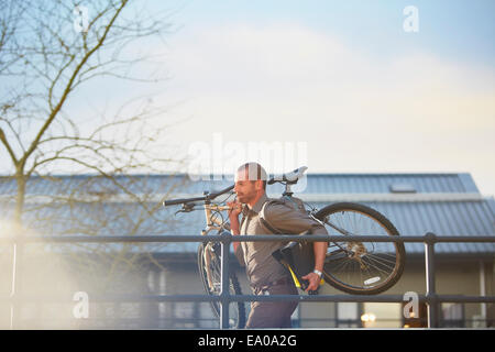 Businessman running with bicycle and folder in arms - Stock Photo