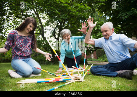 Grandparents and granddaughter playing giant pick up sticks - Stock Photo