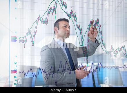 Asian businessman inspecting graph on interactive display - Stock Photo