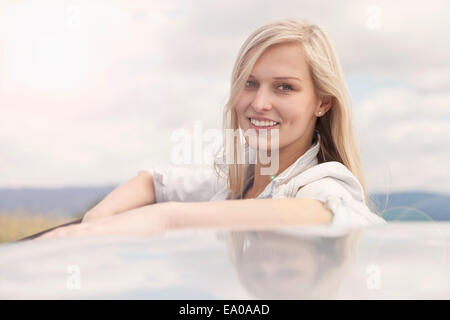 Young woman smiling beside car - Stock Photo