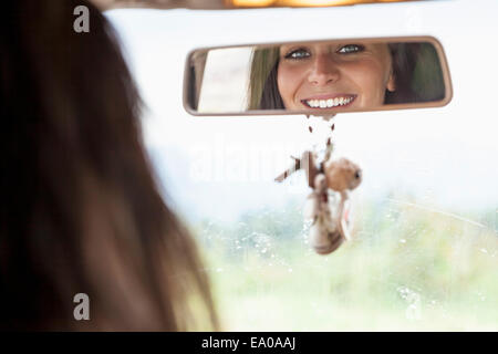 Young woman looking in rear view mirror - Stock Photo