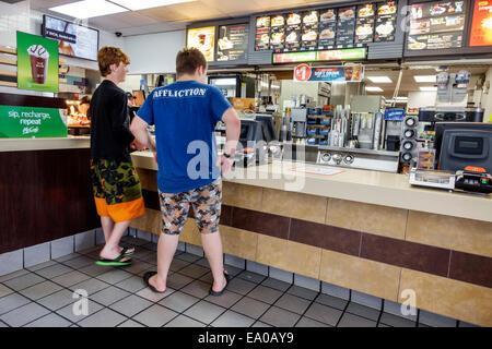 Florida Okeechobee McDonald's restaurant fast food inside counter teen boy friends customers - Stock Photo