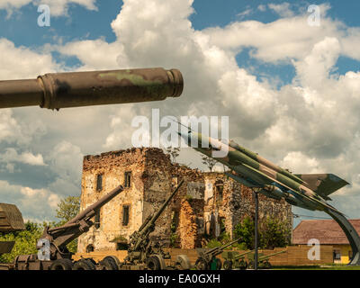 Combination image of tank gun barrel, Jet Fighter and field guns, with dilapidated building in background. - Stock Photo