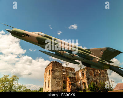Jet fighter, side view, with dilapidated building in background. - Stock Photo