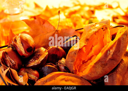 some roasted chestnuts and sweet potatoes in a basket with autumn leaves - Stock Photo
