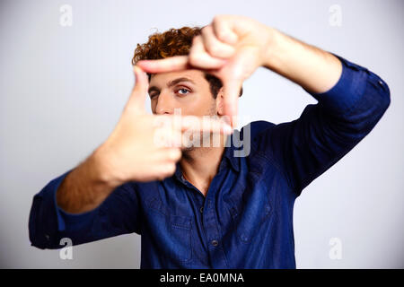 Man framing photograph over gray background - Stock Photo