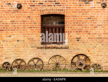 Row of old rusty cart wheels against barn - Stock Photo