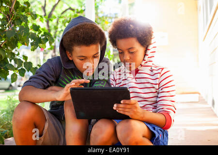 Two brothers using touchscreen on digital tablet in garden - Stock Photo
