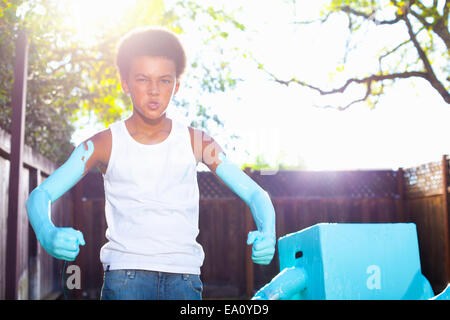 Portrait of boy with blue painted arms in front of home made robot - Stock Photo