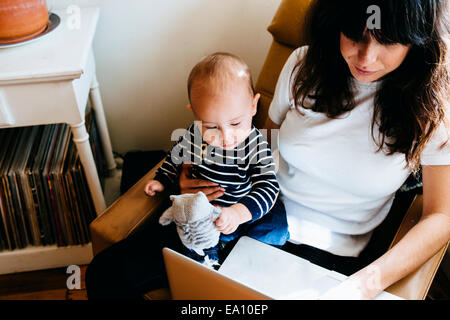 Mother using laptop with son on lap - Stock Photo