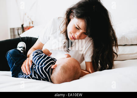 Mother looking down at son on bed - Stock Photo