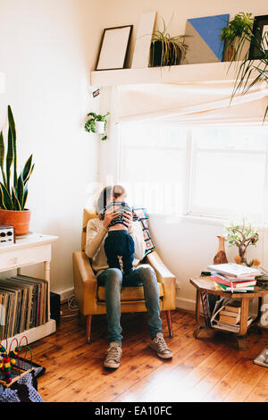 Father sitting on sofa with son - Stock Photo