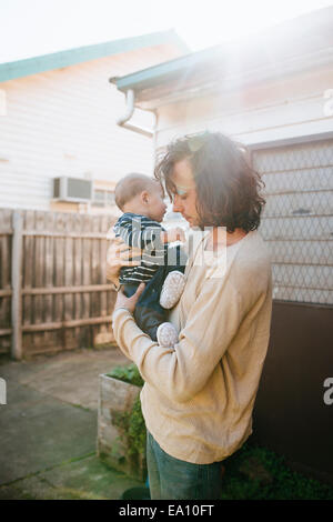 Father with son in arms beside house - Stock Photo