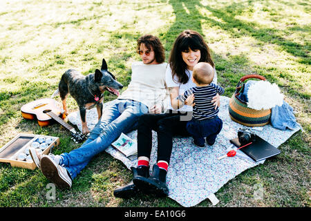 Couple with baby on picnic blanket in park - Stock Photo
