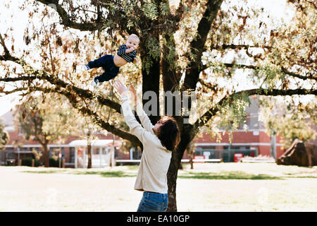Father throwing son in air - Stock Photo