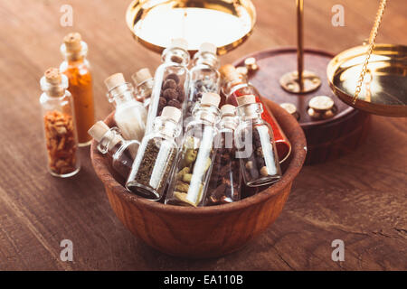 Little bottles with spices in a wooden bowl in the kitchen. Retro decorations - Stock Photo