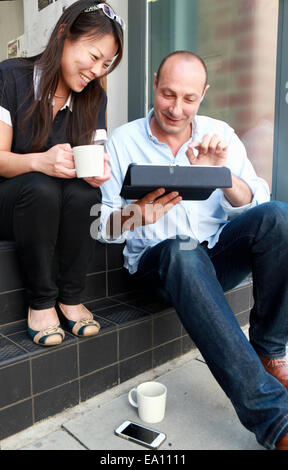 Two architect colleagues looking down at digital tablet on office step - Stock Photo