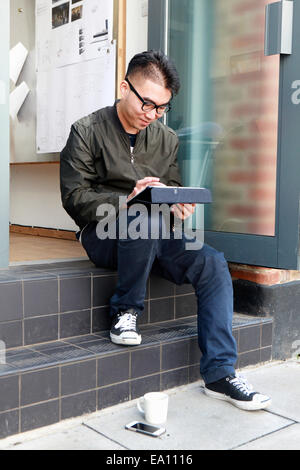 Male architect using digital tablet on office step - Stock Photo