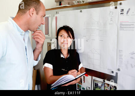 Male and female architects looking at blueprints in office - Stock Photo
