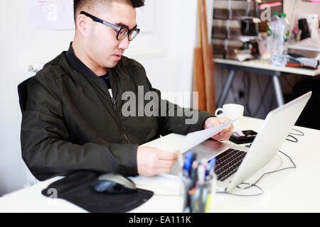Male architect reading paperwork at office desk - Stock Photo