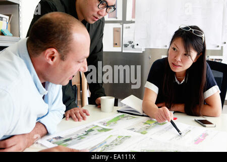Team of three architects discussing ideas for blueprint in office - Stock Photo