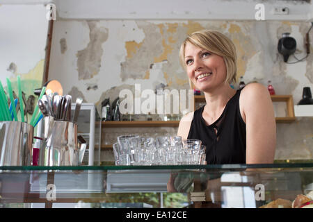 Mid adult woman working in cafe - Stock Photo