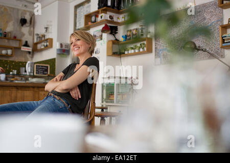 Mid adult woman sitting in cafe - Stock Photo