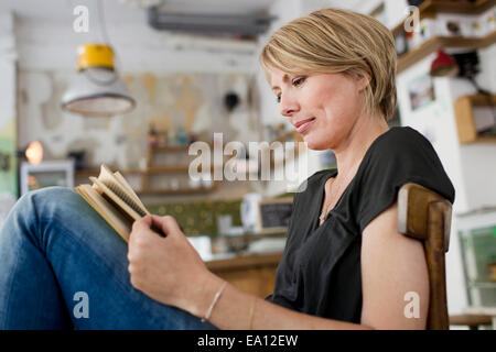 Mid adult woman reading book in cafe - Stock Photo