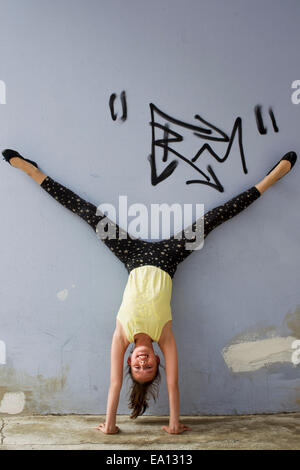 Teenage girl doing handstand against wall - Stock Photo