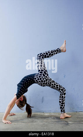 Teenage girl doing backwards bend - Stock Photo