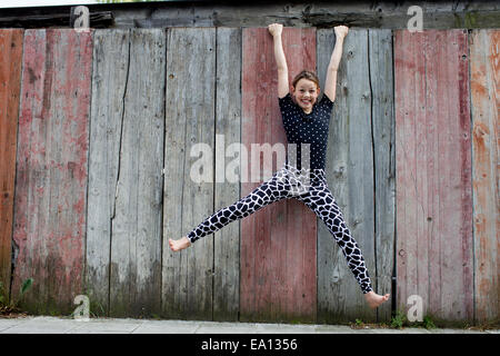 Teenage girl hanging from wooden fence - Stock Photo