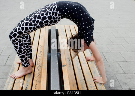 Teenage girl doing backwards bend on bench - Stock Photo