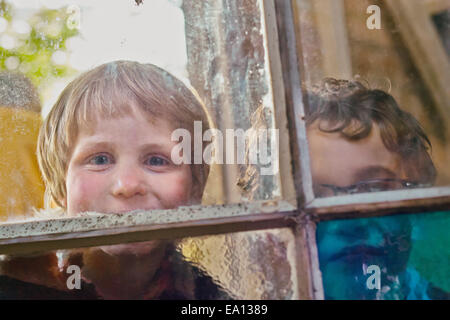 Portrait of two boys looking through hut window - Stock Photo