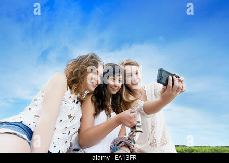 Three young women in field posing for selfie on smartphone - Stock Photo