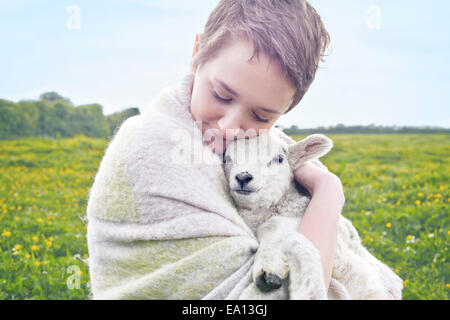 Portrait of young woman in field carrying lamb and wrapped in blanket - Stock Photo
