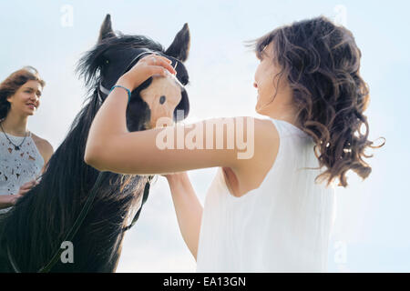 Low angle view of young woman on horse - Stock Photo