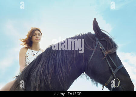Portrait of young woman on horse - Stock Photo