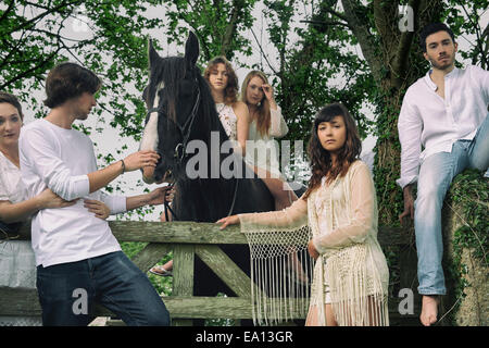 Portrait of six young adults and horse at forest gate Stock Photo