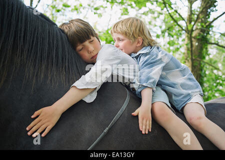 Cropped shot of two brother riding on horse - Stock Photo