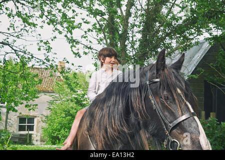 Three boys riding on horse at farm - Stock Photo