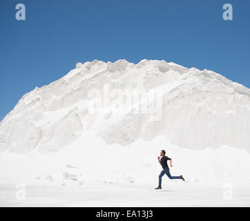 Man running in front of white mountain - Stock Photo