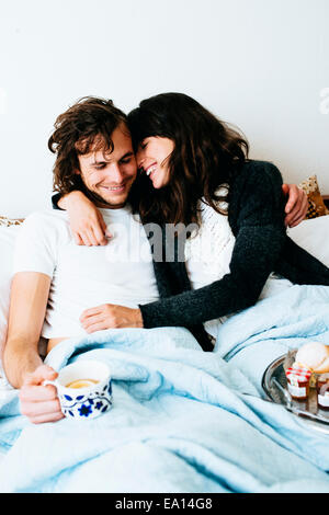 Couple having breakfast in bed - Stock Photo
