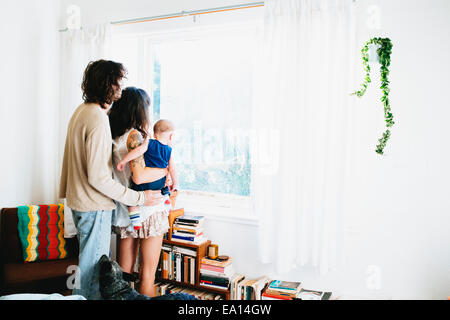 Family looking out of window - Stock Photo