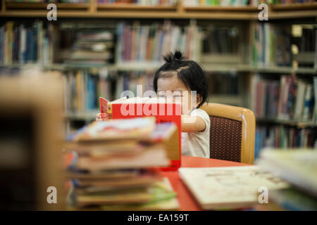One year old baby girl reading book in library - Stock Photo
