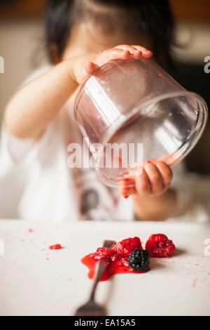 One year old baby girl holding fruit container upside down in highchair - Stock Photo