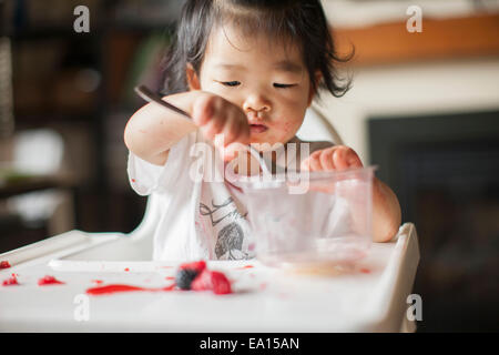 One year old baby girl eating fruit in highchair - Stock Photo