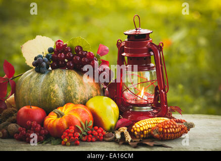 Fruits and nuts, pumpkins on the table outdoor and kerosene lamp - cozy autumn - Stock Photo