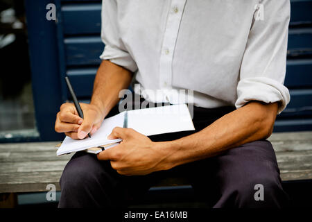 Man writing in notebook - Stock Photo