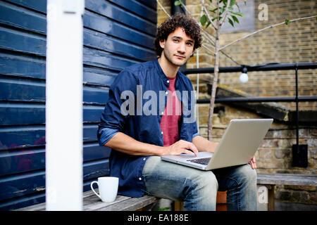 Man using laptop on bench - Stock Photo